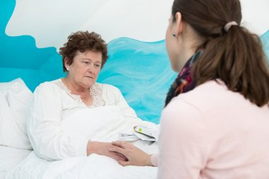 Illness: Older woman lying sick in the bed.