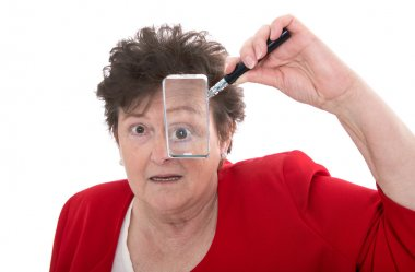 Older isolated woman holding magnifying glass and is shocked.