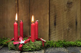 Advent or christmas wreath with four red wax candles.