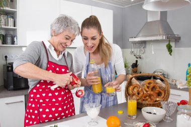 Mother and daughter preparing breakfast together.