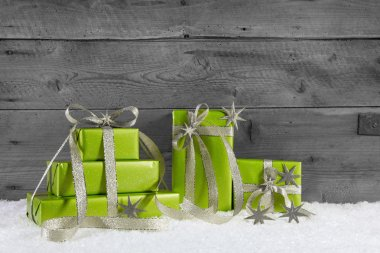 Green gift boxes for christmas on grey shabby background.