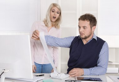Shocked businessman sitting at desk controlling expenses and out
