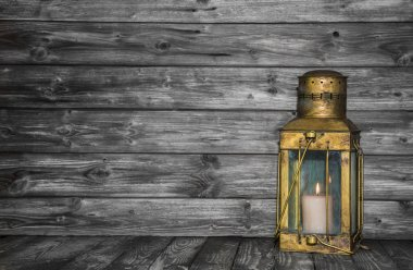 Old rustic golden lantern on wooden old shabby background for co