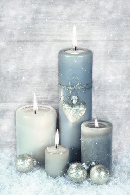 Four blue, grey and white burning christmas candles with snow in