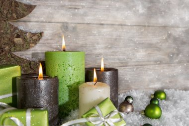 Four burning advent candles in green and brown on wooden backgro