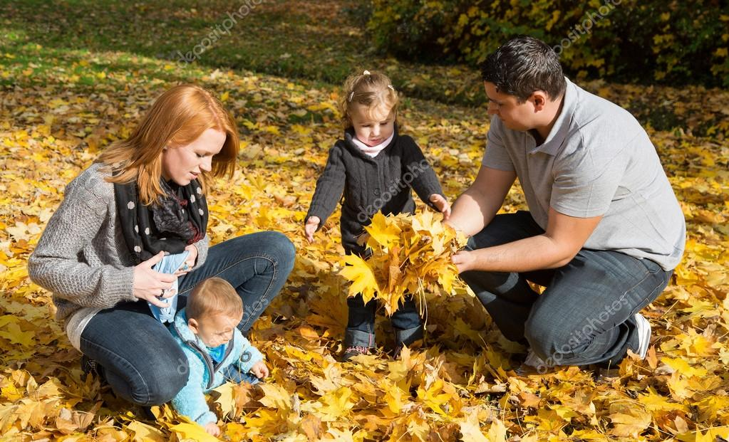 Happy young family in autumn making a walk and play with maple l