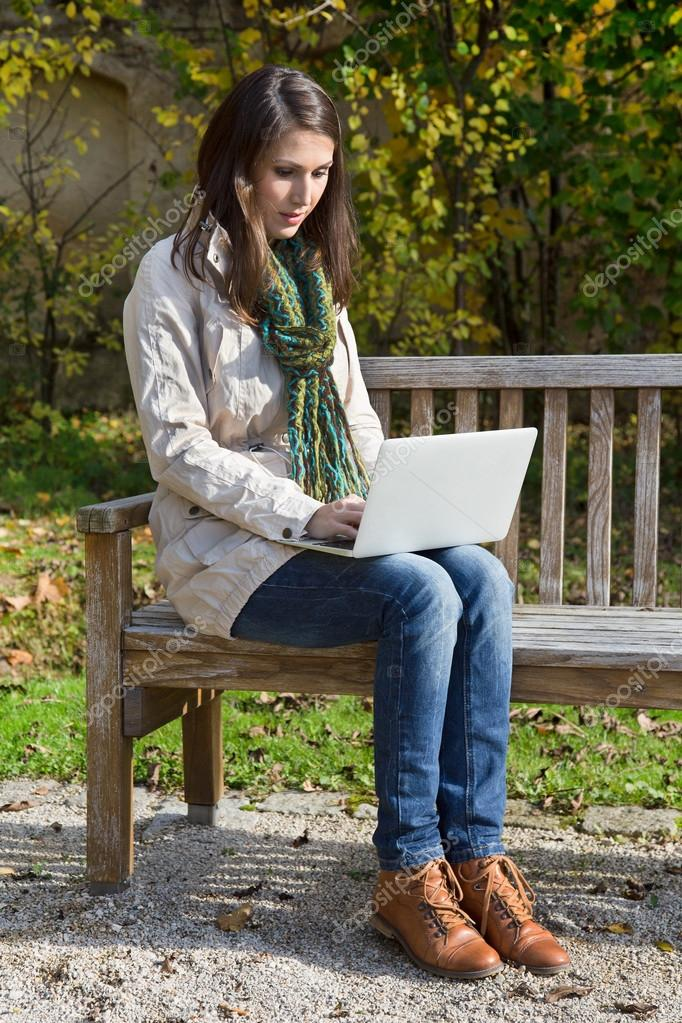 Young woman in autumn sitting on a park bench writing something