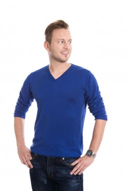 Isolated young blond man in blue pullover looking sideways to te