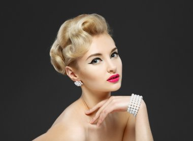 Beautiful young girl with jewels. Makeup in sixties style