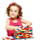 malá dívka staví dům z plastových bloků