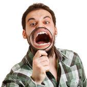 Fotografie ein Mann schreit. krummen Zähne durch eine Lupe zu sehen
