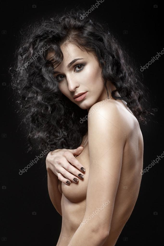 Portrait of sexual girl with a naked breast. Long black hair cur