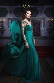 Krásná žena v zelené dlouhé šaty na pozadí bohatě