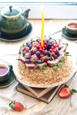 Napoleon cake, decorated with fresh berries, strawberries, blueberries and blackberries, with birthday candle. Two green tea cups and teapot near the window.
