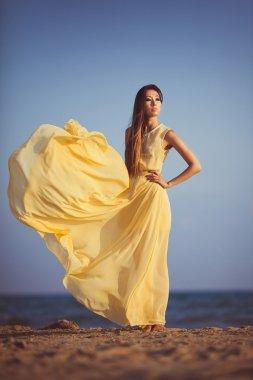 Beautiful fashionable model on the beach in beautifu long dress
