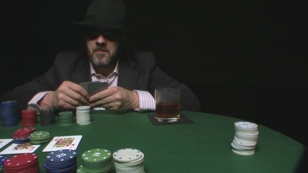 uomo con cappello e occhiali di sole scommesse in un gioco di poker