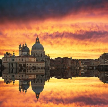 Gorgeous sunset over Grand Canal and Basilica Santa Maria della Salute with beautiful reflections, Venice, Italy