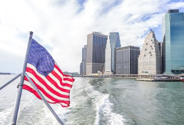 View of Manhattan skyline and flag of USA