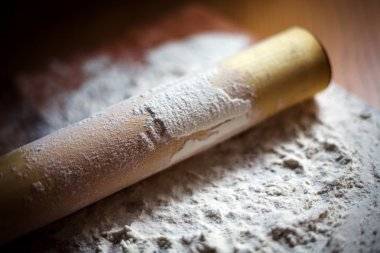 flour with a rolling pin on a cutting board