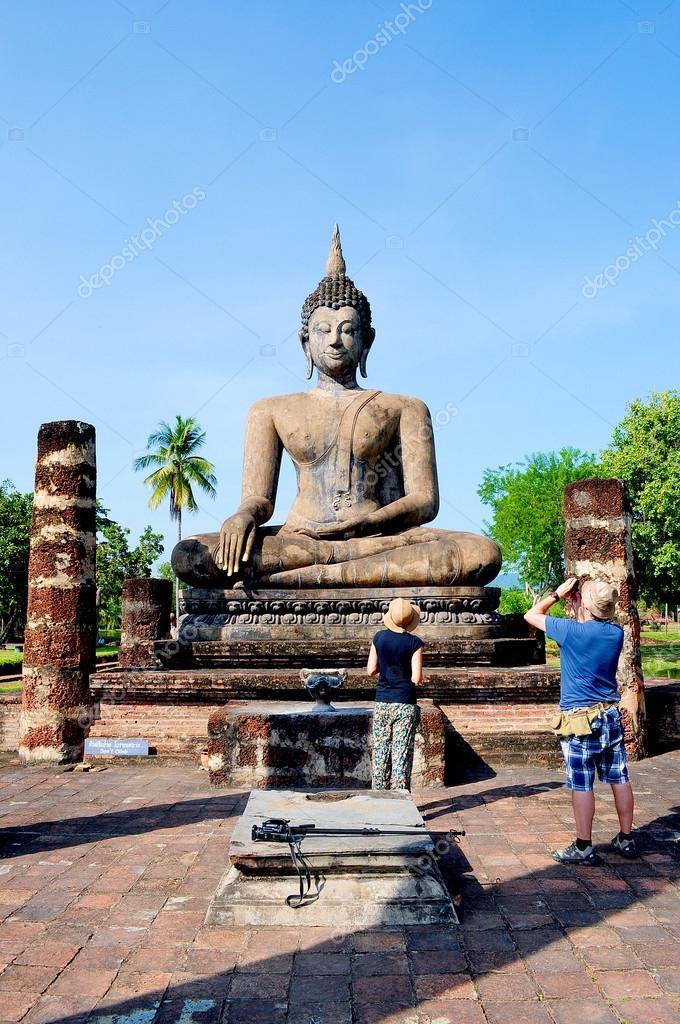 Tourist taking photo of Ancient Buddha image in Sukhothai Histor