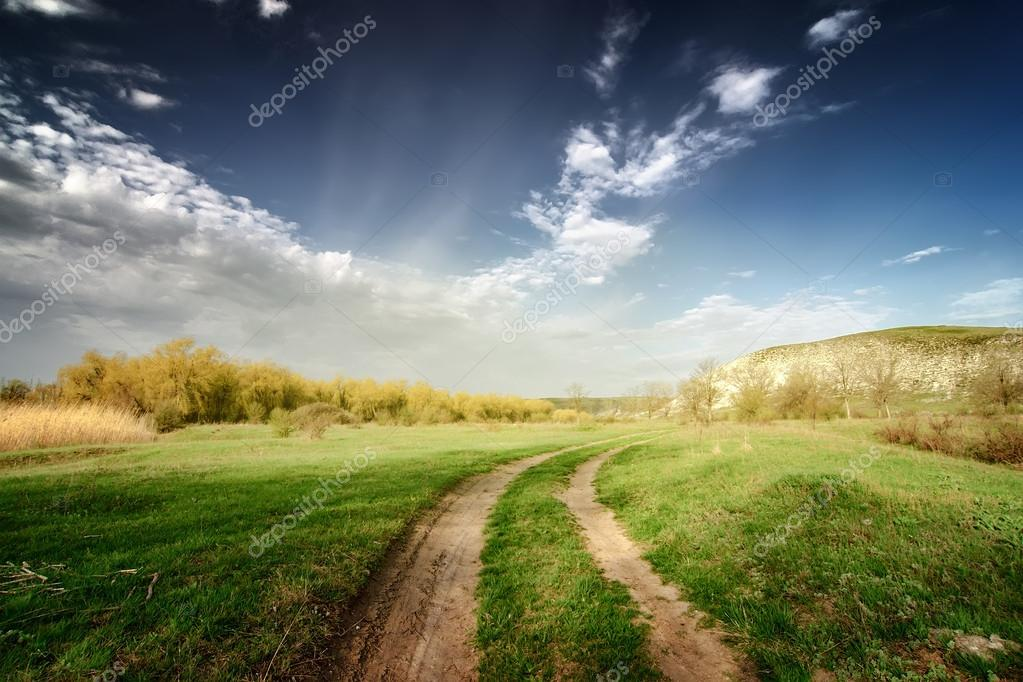 vinage road through fields with green grass and blue sky with cl