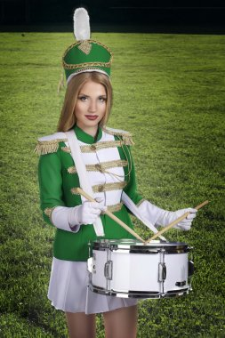 beautiful blonde cheerleader drummer with drum on the background of green grass