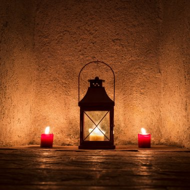 Vintage candlelit in metal lantern standing in stone wall niche