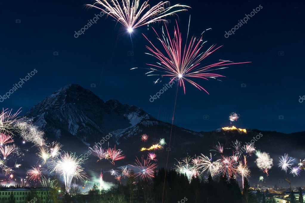 Rockets firework at new years day in front of snowy mountains