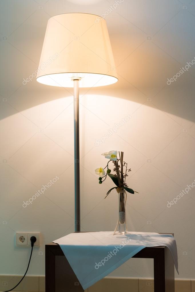 Lampe Lumineuse En Face Du Mur Avec La Fleur Sur La Table