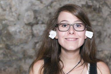 Pretty geek girl with eyeglasses and ear plugs in her ears