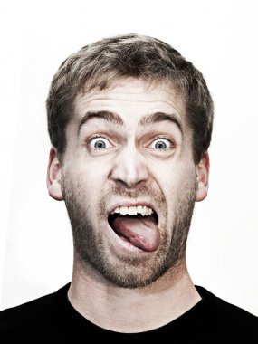 Young blonde man makes grimace with mouth wide open and tongue outside