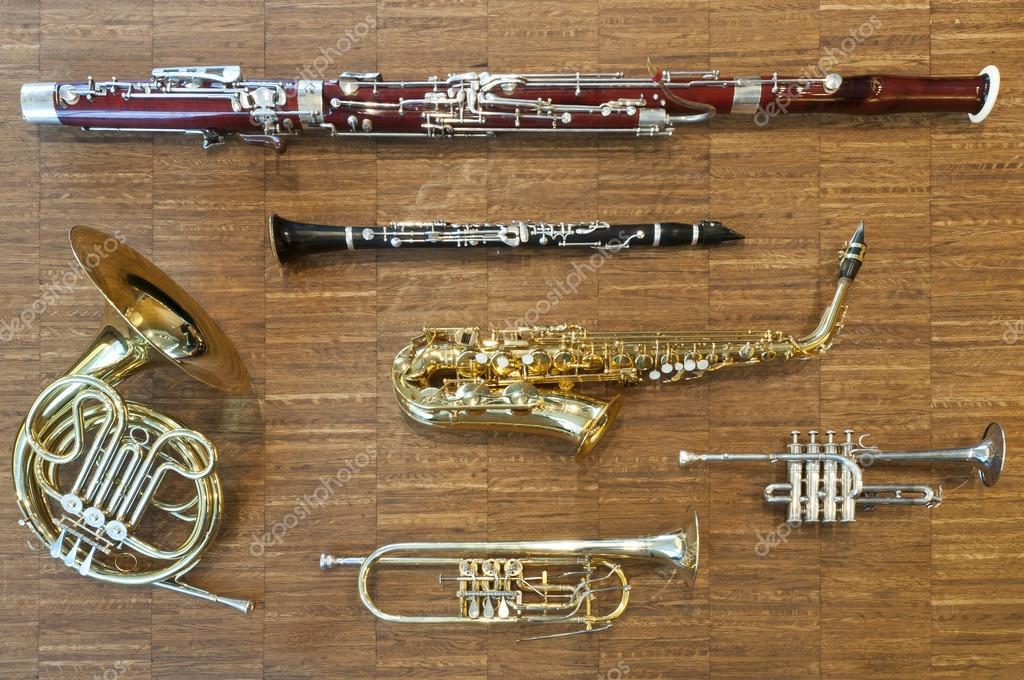 Verschillende blaasinstrumenten tot op een houten vloer trompet