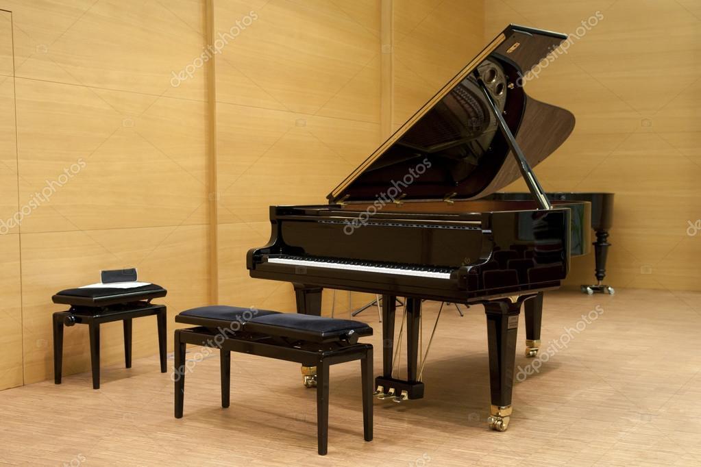 Un pianoforte nero pronto per giocare con sgabello di fronte su un
