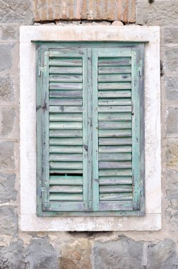 Old window with blue closed shutters on an old house
