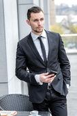 a hívásvárakoztatást. fiatal üzletember hivatalos viselni, holding sejt ph