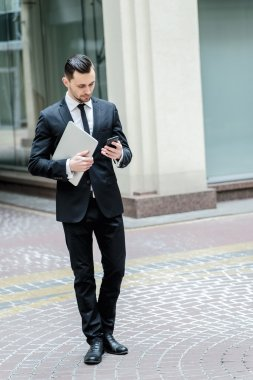 To meet clients. Confident businessman with laptop goes ahead an