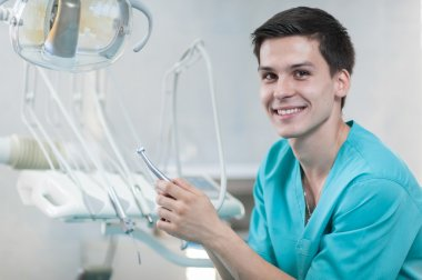 Dentist holding a dental drill in hand.