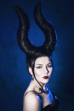 Beautiful woman from a fairytale with a hair horns and jewelry in a spotlight with blue backlight looking at camera