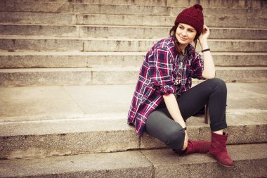 Brunette woman in hipster outfit sitting on steps on the street. Toned image. Copy Space