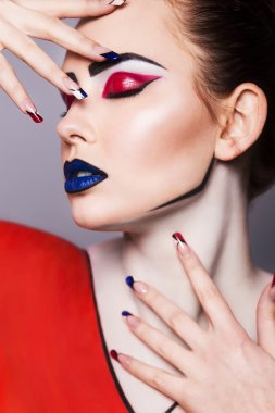Beautiful brunette woman with creative pop art make up and geometric nail style, black lines and closed eyes