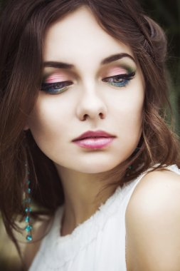 Portrait of a beautiful brunette woman in white dress and colorful make up outdoors