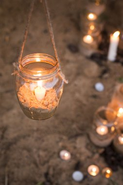 Beautiful decorated romantic place for a date with jars full of candles hunging on tree and standing on a sand