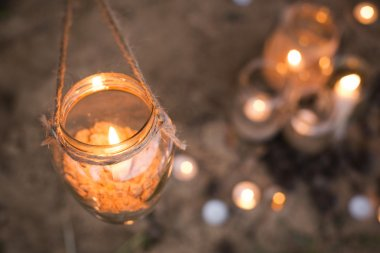 Beautiful decorated romantic place for a date with jars full of candles hunging on tree and standing on a sand. Copy Space