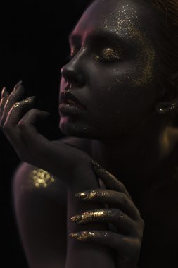Close up portrait of a Woman on black background with the glitters and sparkles all over the black skin