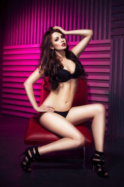 Brunette sexy woman in black underwear and heels in studio in red light sitting on a sofa. Indoors