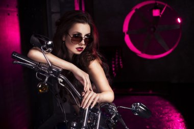 Brunette sexy woman in black underwear, heels and sunglasses in studio in red light on a motorcycle. Indoors. Copy Space