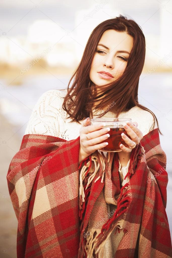 Brunette woman outdoors in check pattern plaid drinking tea and looking down near the lake