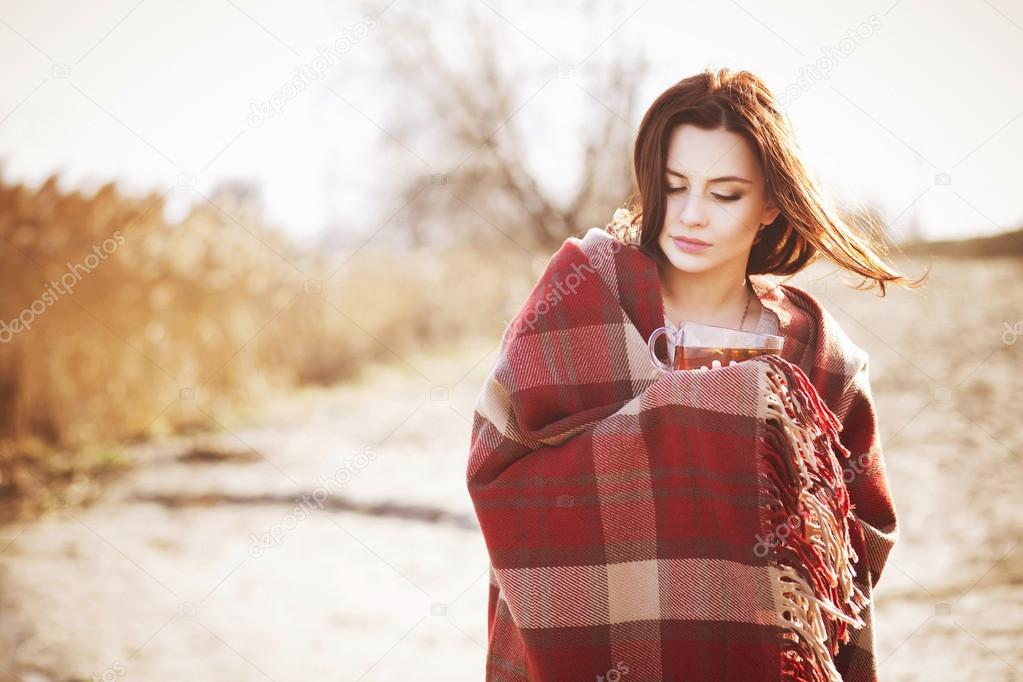 Brunette woman outdoors in check pattern plaid drinking tea and looking down near the lake. Copy space