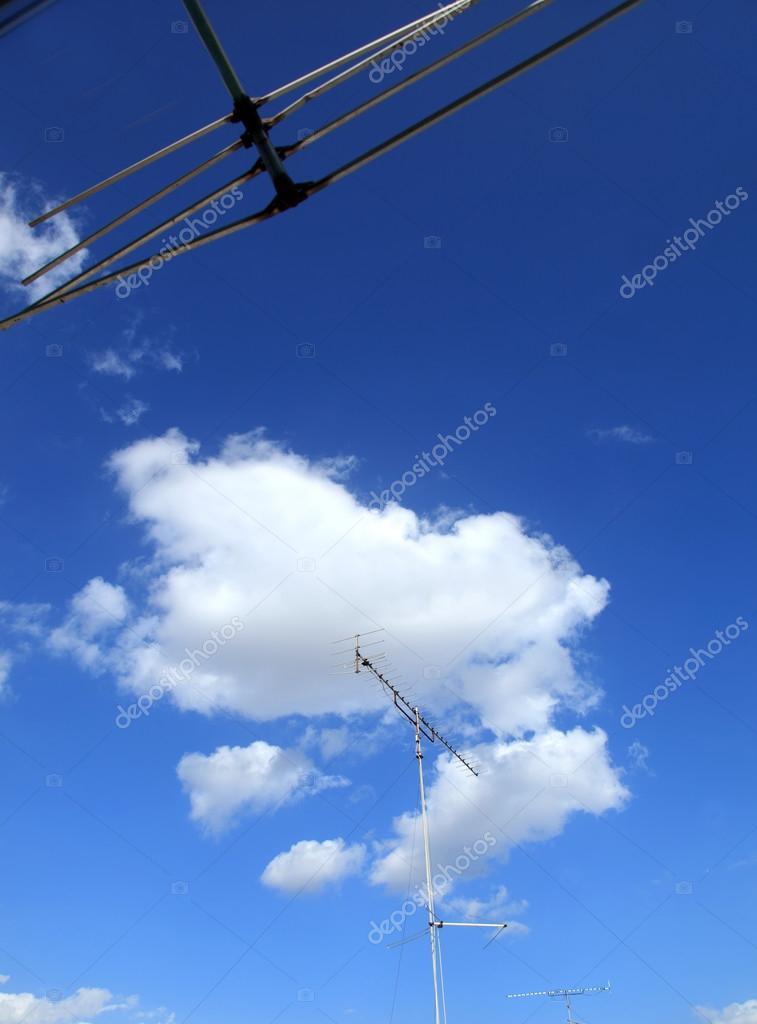 Home TV antennas on blue sky