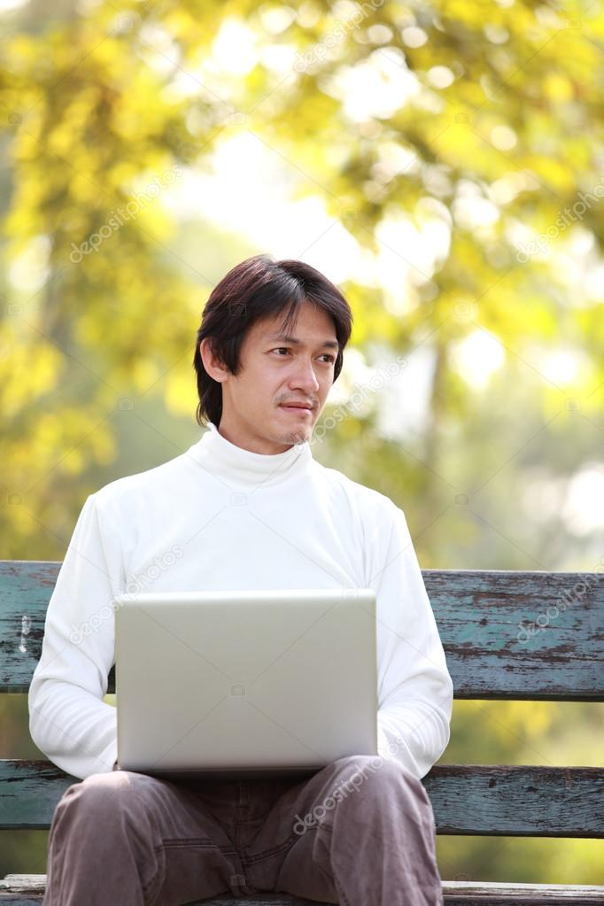A young handsome man using laptop sitting on a bench looking in